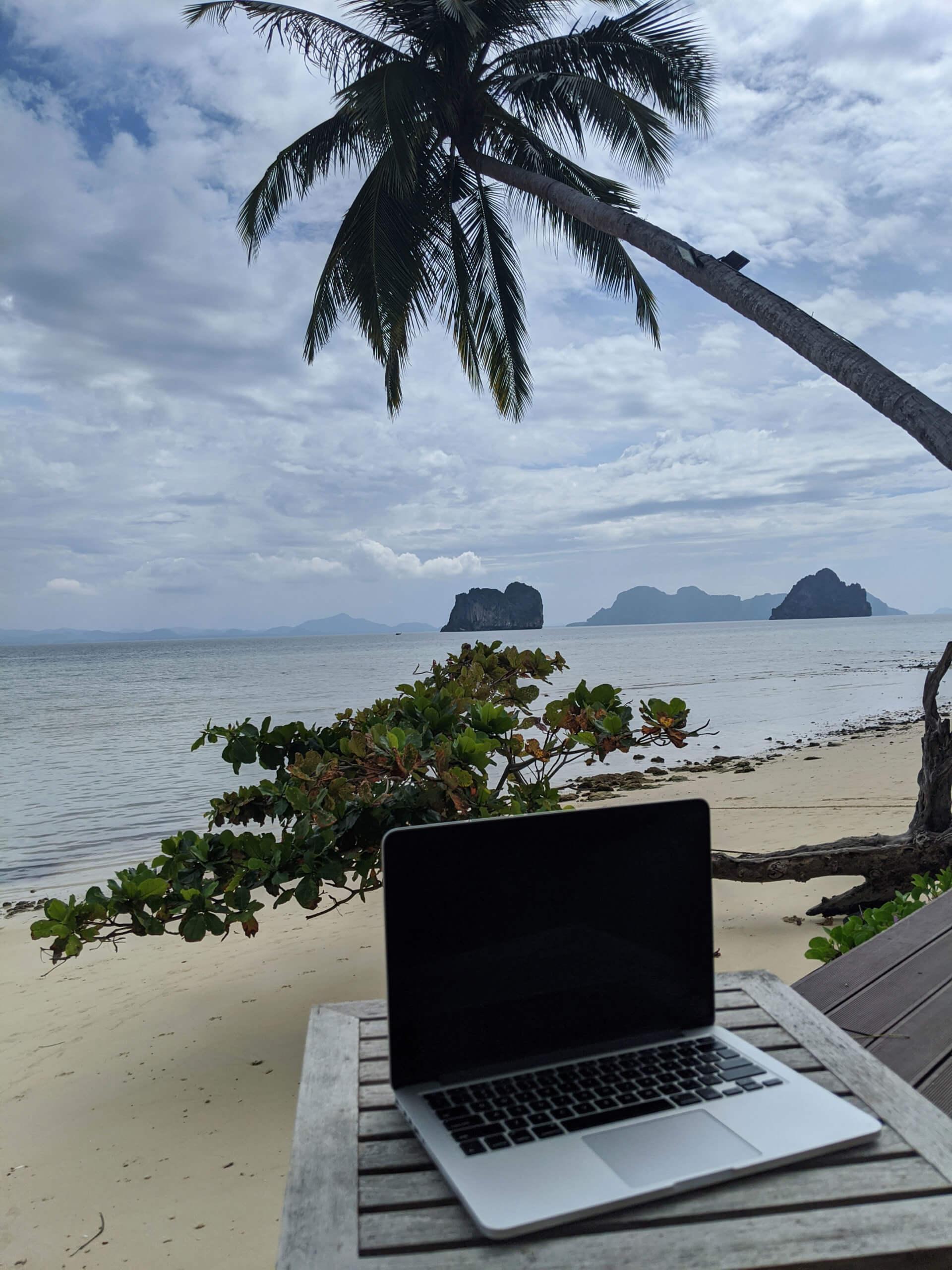 komputer na plaży w tajlandii z widokiem na może i palme